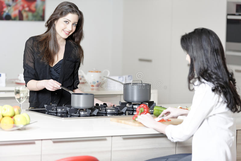 Two friends in a kitchen cooking. Two friends in a kitchen catching up preparing dinner royalty free stock images