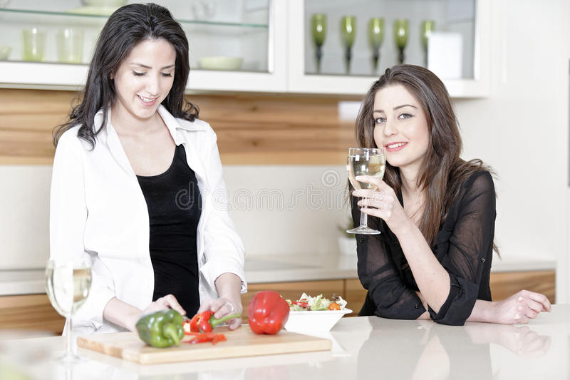Two friends in a kitchen cooking. Two friends in a kitchen catching up preparing dinner royalty free stock photography