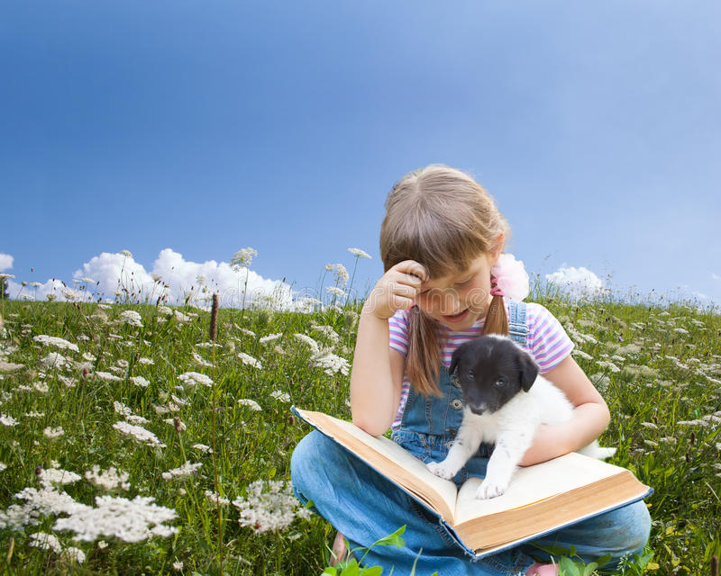 Two friends- little girl and puppy. A girl reading book with little puppy in garden royalty free stock photo