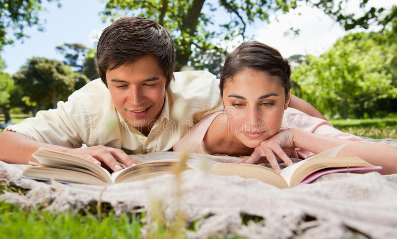 Two Friends Looking Down At Books While Lying On A Blanket Stock Photo