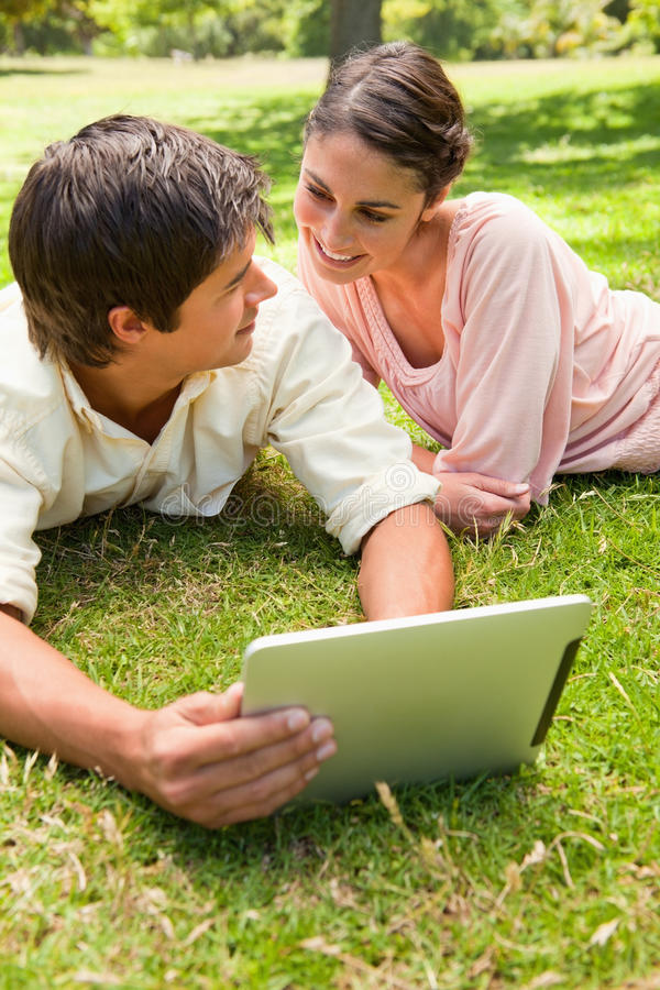 Download Two Friends Looking At Each Other While Using A Tablet Together Stock Image - Image of cute, male: 25332567
