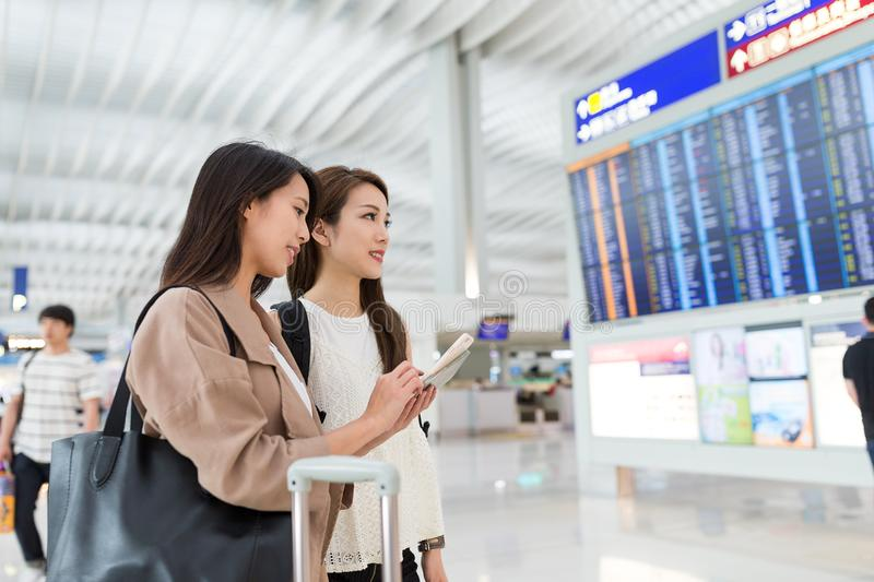Two friends looking for flight number. Beautiful young asian woman royalty free stock image