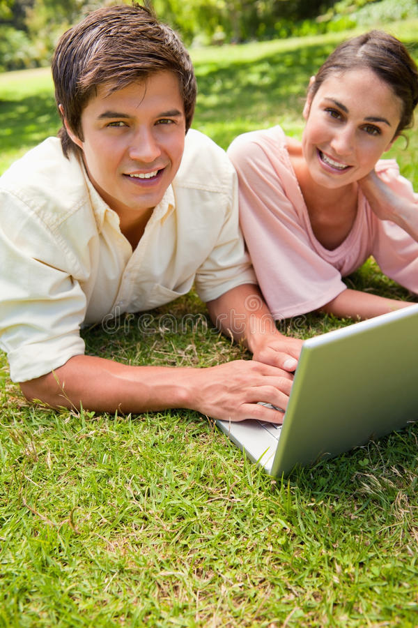 Download Two Friends Looking Towards The Side While Using A Laptop Stock Photo - Image: 25332546