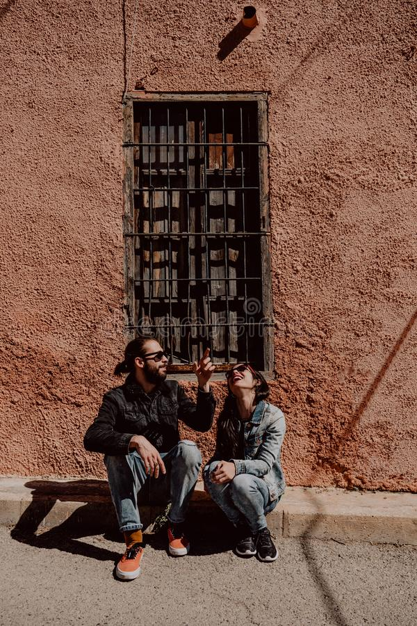 Two friends man and woman, happy, smiling, sitting on the street with sunglasses outdoors royalty free stock image