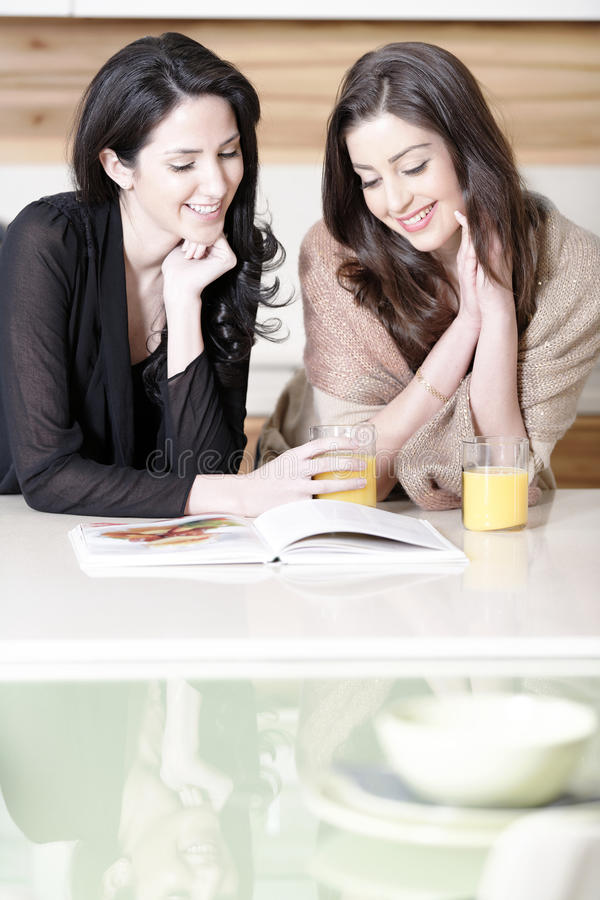 Two friends reading recipes. Two attractive young women reading from a cookery book in a kitchen stock image