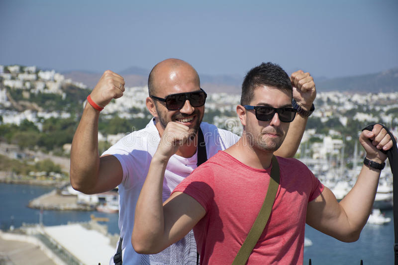 Two friends showing off his muscles. While posing for a photo on a sea resort background royalty free stock photo