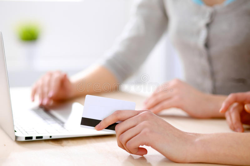 Two friends or sisters making on line shopping by credit card stock photography