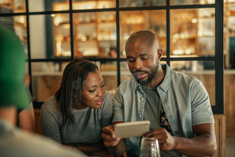 Two friends sitting in a bar looking at cellphone photos royalty free stock image