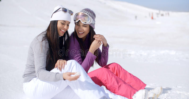 Two Friends Sitting Together on Sunny Ski Hill stock photos