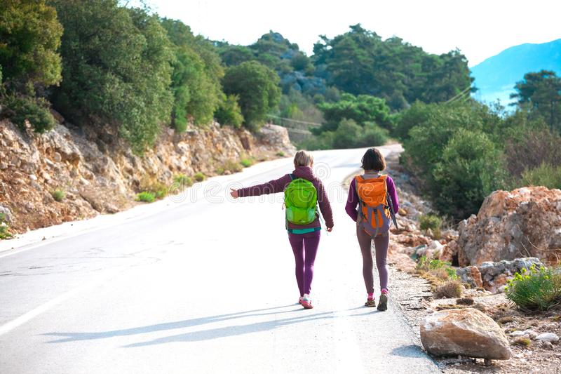 Two friends stop the car. Hitchhiking. Women catch the car on a mountain road. Girls with backpacks are on a mountain road. Free transport stock photos