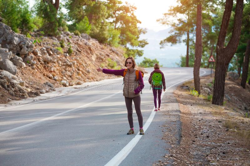 Two friends stop the car. Hitchhiking. Women catch the car on a mountain road. Girls with backpacks are on a mountain road. Free transport stock photography