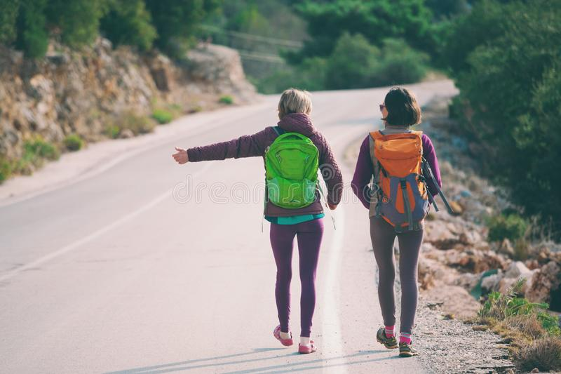 Two friends stop the car. Hitchhiking. Women catch the car on a mountain road. Girls with backpacks are on a mountain road. Free transport royalty free stock images