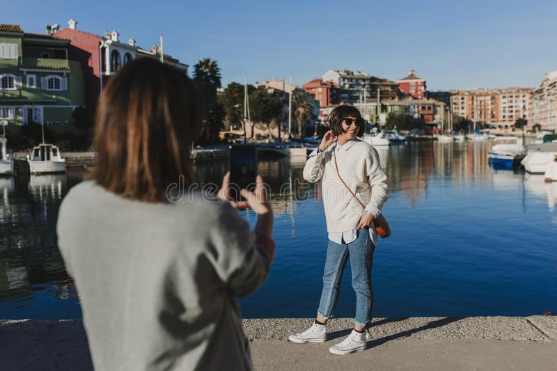Two friends in the street taking pictures with mobile phone. Port background in a sunny day. Lifestyle outdoors. friendship royalty free stock images