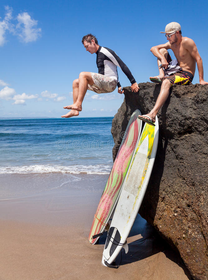 Two friends surfer on rock. Two positive friends surfer on a rock. Two surfboards standing on the sand, leaning on a rocky big stone royalty free stock photos