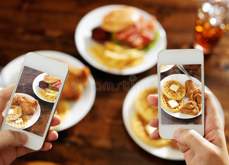 Two friends taking photo of their food with smartphones royalty free stock image