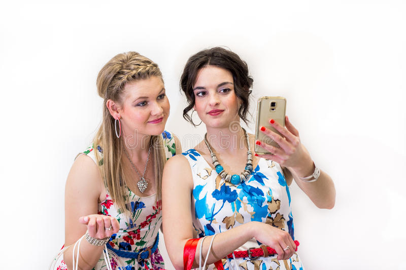 Two friends taking a selfie with smart phone. Fashion and beauty holding shopping bags royalty free stock photography