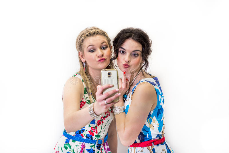 Two friends taking a selfie with smart phone. Fashion and beauty pouting lips royalty free stock photos