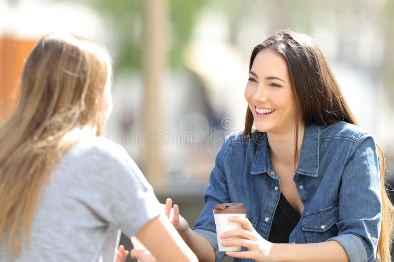 Two friends talking drinking coffee in a park. Two happy friends talking drinking coffee sitting in a park a sunny day stock photos