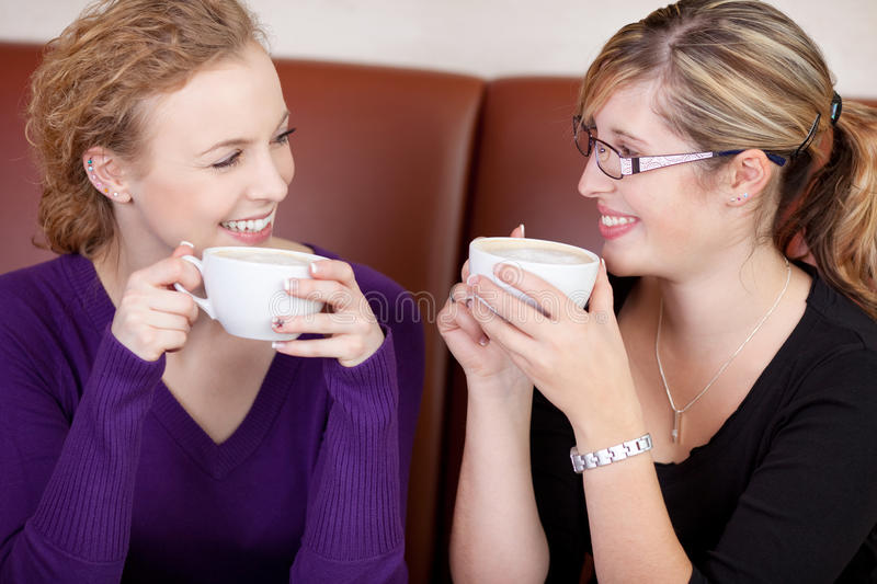Two friends talking and having coffee. Two females talking and having coffee in caf stock photos
