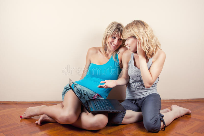 Two friends talking with laptop royalty free stock photo