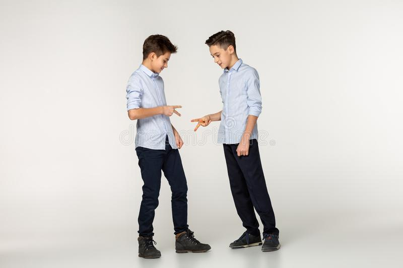 Two friends teenagers in blue shirts playing a game of stone, paper and scissors royalty free stock images