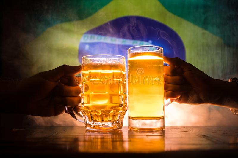 Two friends toasting (clinking) with glasses of light beer at the pub. Beautiful background with blurred view of flag of Brazil. S. Upport your country with beer royalty free stock image