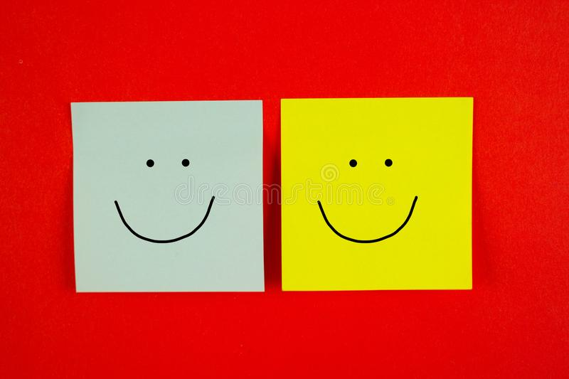 Two friends together. Two pieces of paper with happy smile stock photo
