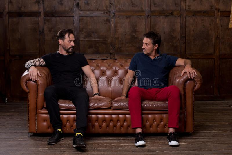 Two friends touching the sofa surface and discussing it. Calm thoughtful middle aged men sitting on the sofa and carefully touching the surface of it while royalty free stock photo
