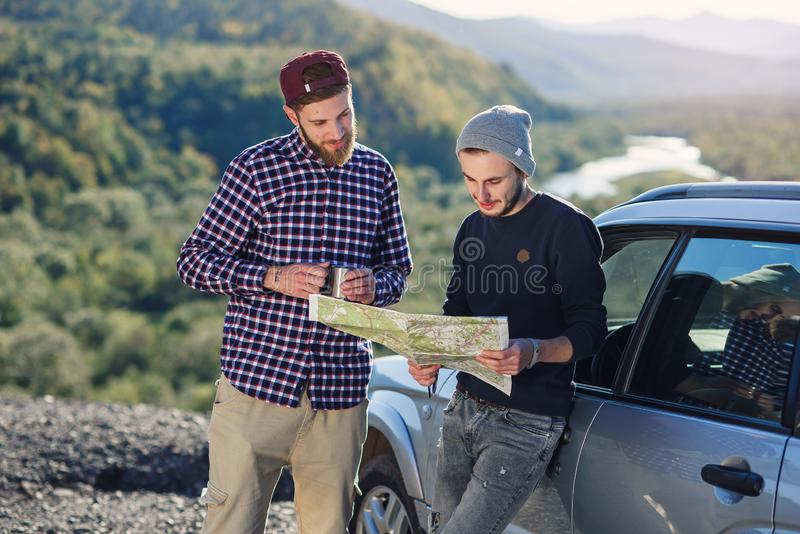 Two friends travelers with cap of tea and looking at the paper map to find correct way. Happy hipster men exploring stock photos