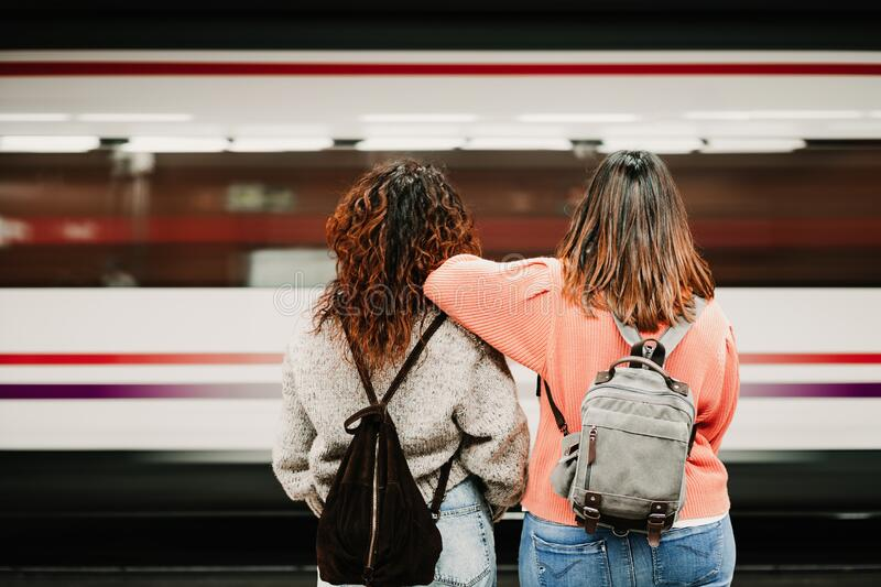 Two friends waiting relaxed and carefree at the station before catching a train. Travel photography. Lifestyle stock photography