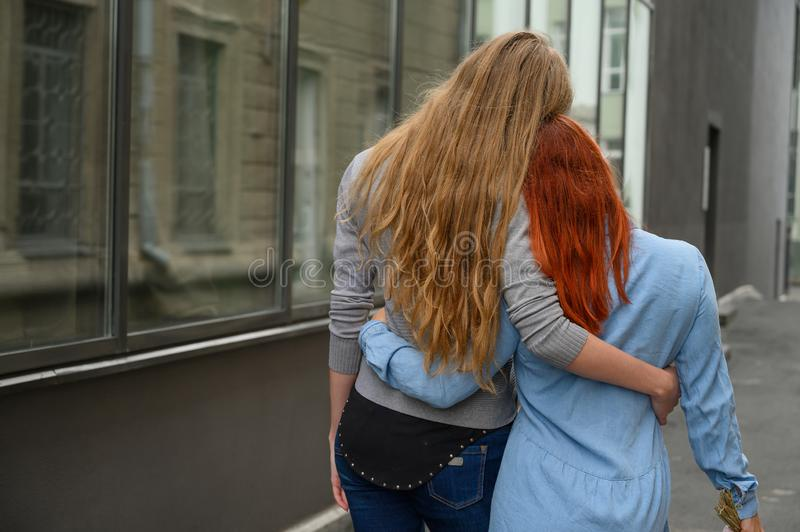 Two friends are walking along the street and gently hugging each other around the waist. The blonde in the jacket and. Two friends are walking along the street royalty free stock image