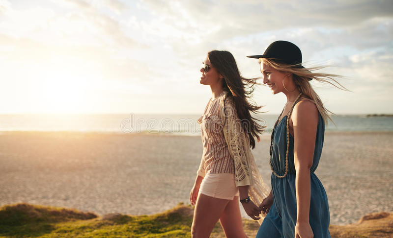 Two friends walking on the beach on a summer day stock photography