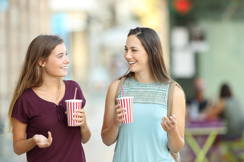 Two friends walking and holding refreshments. Front view of two friends walking towards camera and holding refreshments in the street royalty free stock photo