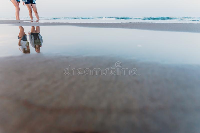 Two friends walking at sunset on a beach, reflecting in the puddles of sand royalty free stock photography