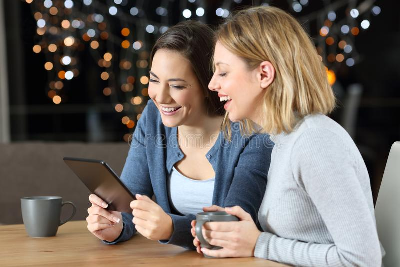 Two friends watching media content in a tablet in the night. Two happy friends watching media content in a tablet sitting in a table at home in the night royalty free stock photography