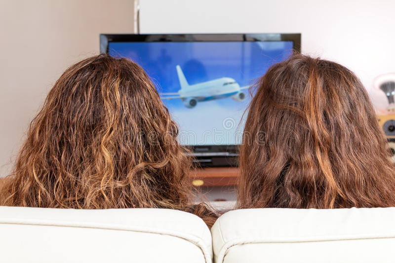 Two friends watching TV stock photo