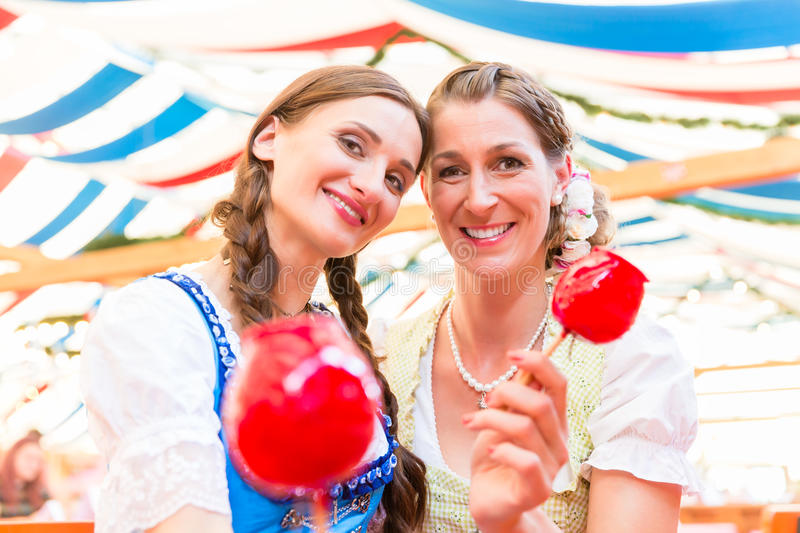 Friends in a beer tent holding candy apples. Two friends wearing dirndl and holding candy apples in a beer tent at Regensburger Dult royalty free stock photography