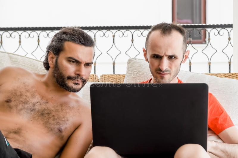 Two friends working on laptop at open air royalty free stock photo