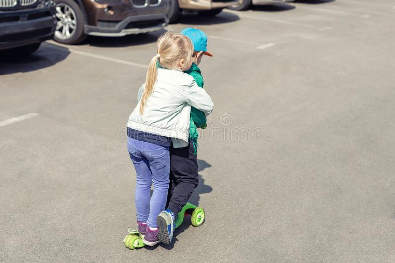 Two frineds boy and girl having fun riding one scooter together simultaneously. Children playing on car parking road. Danger and risk of accident stock photography