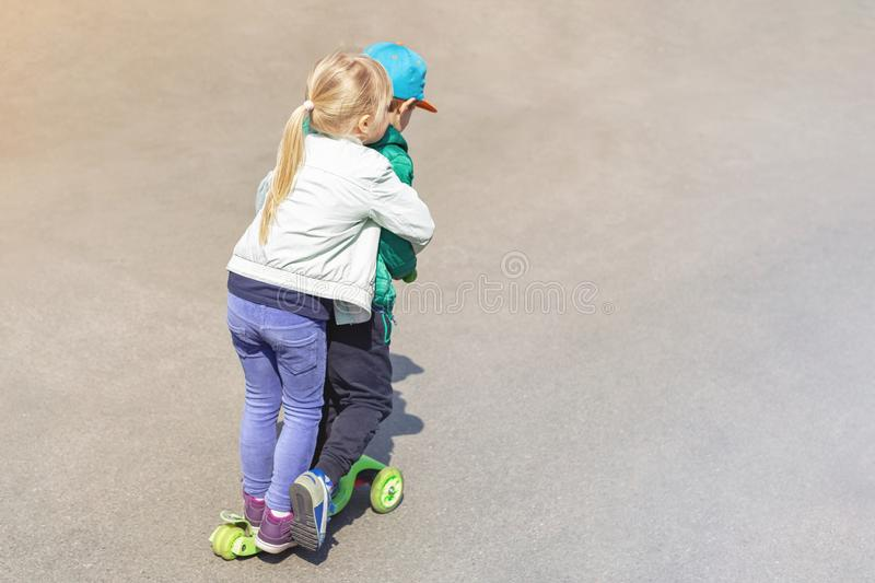 Two frineds boy and girl having fun riding one scooter together simultaneously. Children siblings, brother and sister. Enjoying outdoor sport activities royalty free stock photography