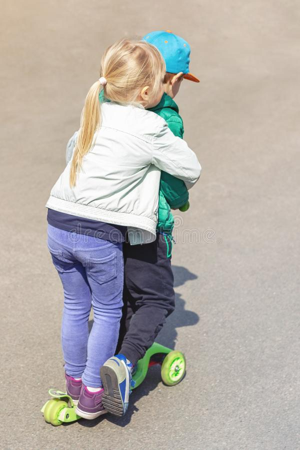 Two frineds boy and girl having fun riding one scooter together simultaneously. Children siblings, brother and sister. Enjoying outdoor sport activities royalty free stock photos