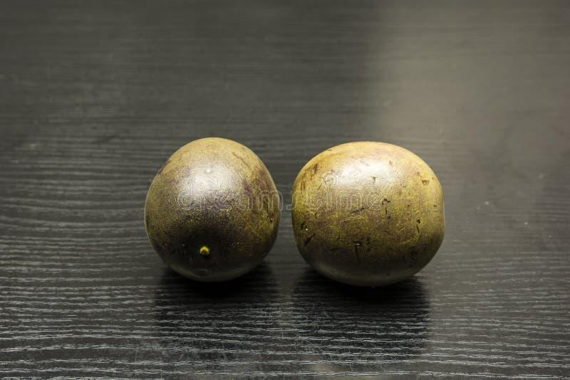 Two fruits of Passiflora edulis. Two ripe fruits of Passiflora edulis on dark wood royalty free stock photos