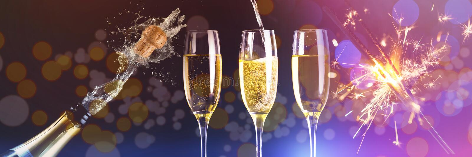 Composite image of two full glasses of champagne and one being filled. Two full glasses of champagne and one being filled against champagne cork popping stock photos