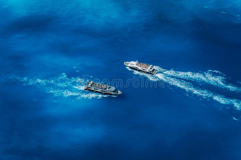 Two fully occupied tourist boats in open sea leaving and arriving in Navagio Beach on Zakynthos Island in Greece stock photos