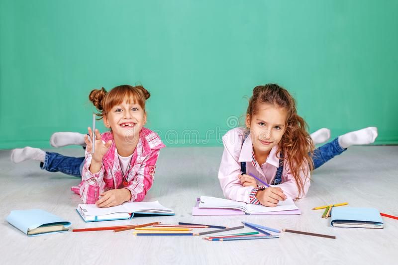 Two fun little children do homework. The concept of childhood royalty free stock photography