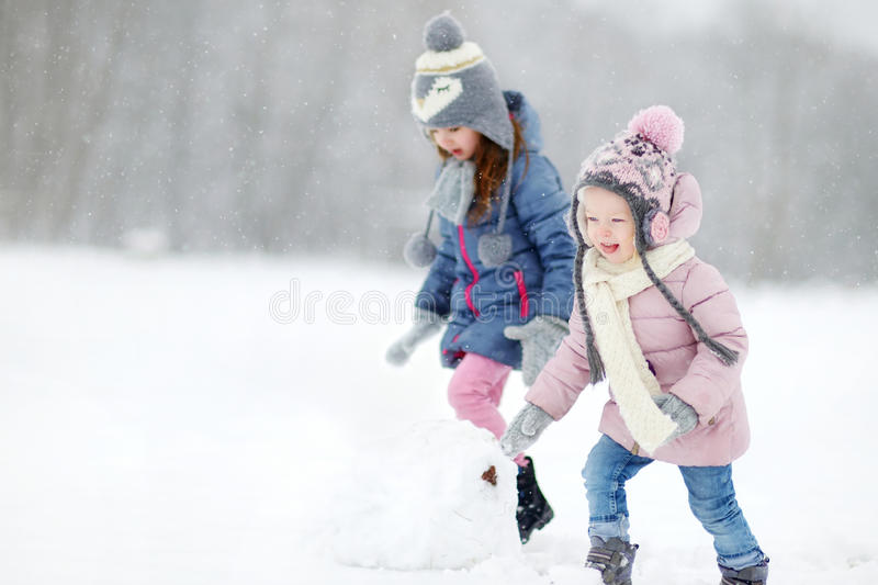 Two funny adorable little sisters in winter park royalty free stock images