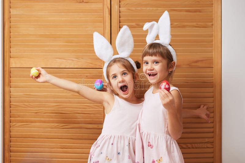 Two funny charming little sisters in the dresses with white rabbit`s ears on their heads holds dyed eggs in their hands royalty free stock image