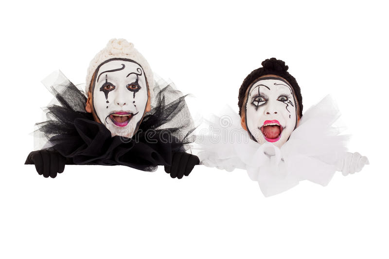 Two funny clowns looking above a frame stock image