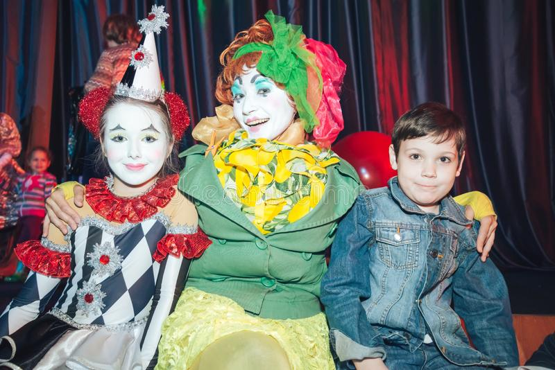 Two funny clowns are photographed with a boy. stock photography