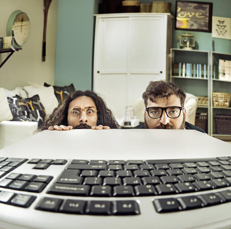 Two funny computer scientits staring at a keybord. Two funny IT specialists staring at a keybord stock images